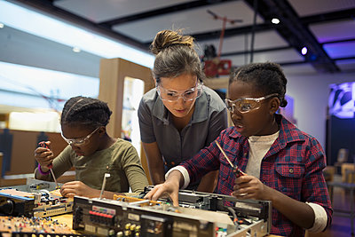 Scientist watching twin sisters assembling electronics in science center - p1192m1194256 by Hero Images