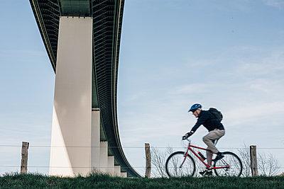 Senior man riding bike, under bridge - p300m1580794 von Gustafsson