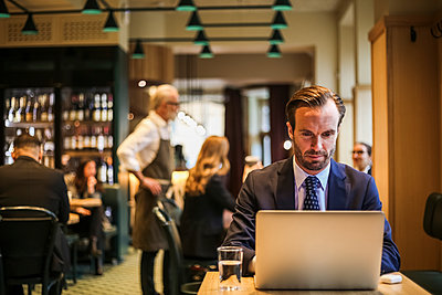 Businessman using laptop while sitting in restaurant - p426m2212054 by Maskot