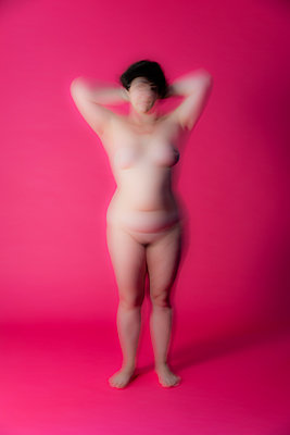 Naked woman in studio, blurred on pink background - p590m2054312 by Philippe Dureuil
