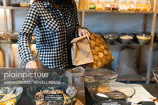 Barcelona, Spain. Woman buying groceries in a market hall. Grocery shopping, customer, market hall, small business, sustainability, food, bag, ecological, woman, selection, positive, paying, local produce, healthy eating, shopping, service, business - p300m2286893 von NOVELLIMAGE