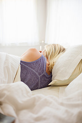 Blonde woman sleeping in a bed with white linen. - p1100m1080246 by Mint Images