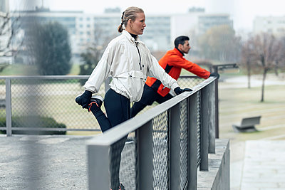 Male and female athletes doing stretching exercise by chainlink fence at public park - p300m2275562 by Josep Suria