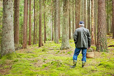 Older man wearing basket looking at forest - p312m1551929 by Johner Images