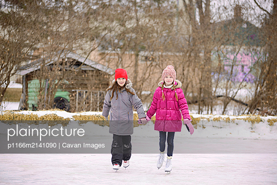 Two Girls Ice Skating Outdoors - p1166m2141090 by Cavan Images