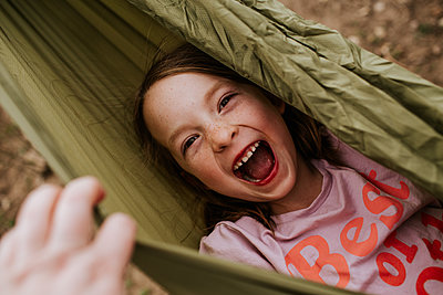 Overhead of silly girl laughing in hammock - p1166m2201342 by Cavan Images