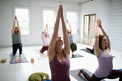 Women practicing yoga low lunge pose in yoga class - p1192m1583320 by Hero Images