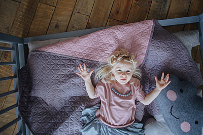 Little girl lying on a bed - p1414m1590588 by Dasha Pears