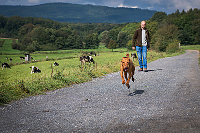 Man walking with his dog - p227m1503290 by Uwe Nölke