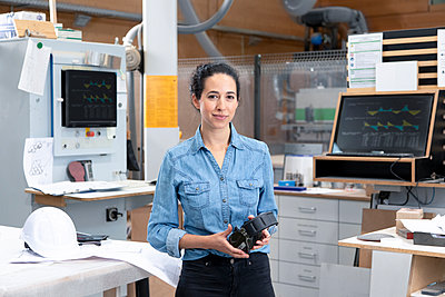 Businesswoman holding ear protectors while standing in factory - p300m2265997 by Florian Küttler