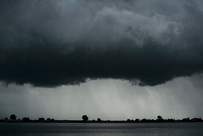 Black and white image of heavy rainfall over lake during thunderstorm - p429m1079904 by Mischa Keijser