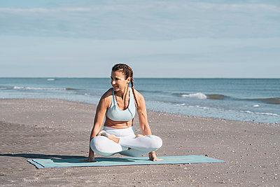 Woman practising yoga on beach - p429m2019411 by Ingolf Hatz