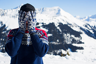 A Person In Knitted Sweater, Cap And Mittens Hides His Face With His Hands    - p847m1102425 by Paulina Westerlind