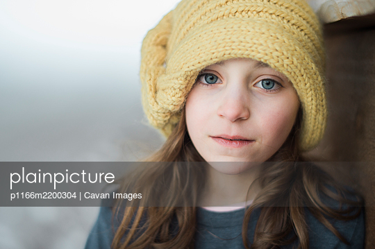 Blue-eyed girl in yellow knit hat - p1166m2200304 by Cavan Images