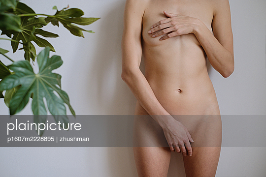 Portrait of a hiding nude woman with a plant - p1607m2228895 by zhushman