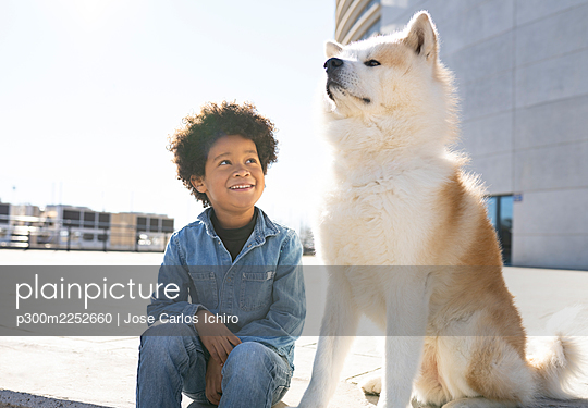 Smiling boy looking at dog while sitting on footpath - p300m2252660 by Jose Carlos Ichiro