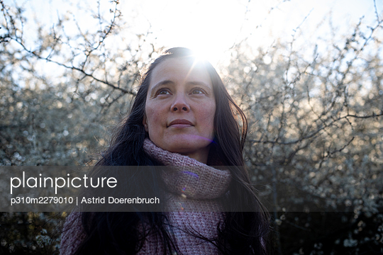 Woman in backlight in front of blackthorn - p310m2279010 by Astrid Doerenbruch