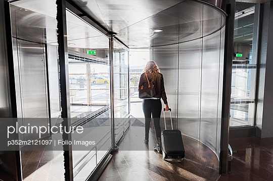 Young woman pulling suitcase - p352m2121097 by Folio Images