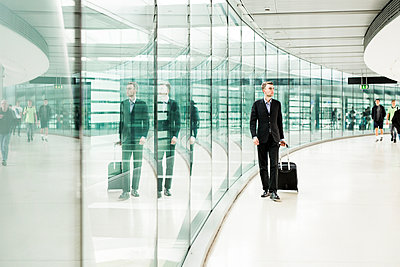 Full length of businessman walking with luggage at airport - p1264m1122109f by Astrakan
