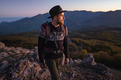 Man against mountain range at sunset - p1427m2163676 by Oleksii Karamanov