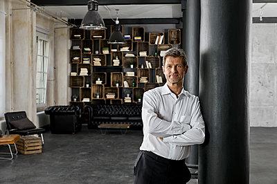Portrait of mature man in loft leaning against a column - p300m1581515 von Philipp Dimitri