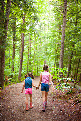 Caucasian sisters walking in forest - p555m1409456 by Shestock