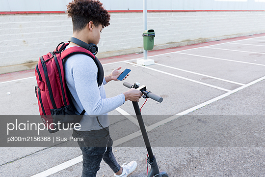 Young man with e-scooter using smartphone - p300m2156368 by Sus Pons