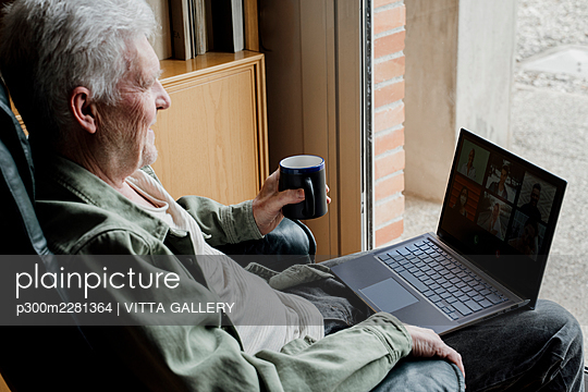 Senior man with laptop holding coffee mug at home - p300m2281364 by VITTA GALLERY