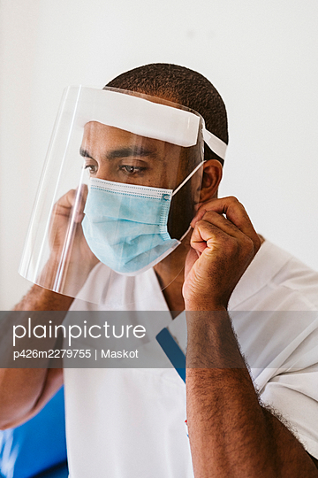 Male doctor wearing protective face mask and face shield during COVID-19 - p426m2279755 by Maskot