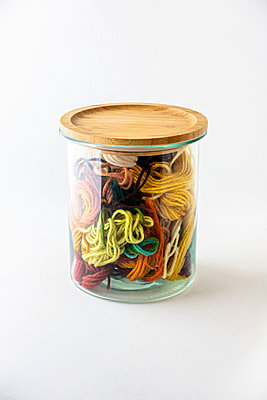 Pieces of wool inside a glass jar with wooden lid - p1302m2214827 by Richard Nixon