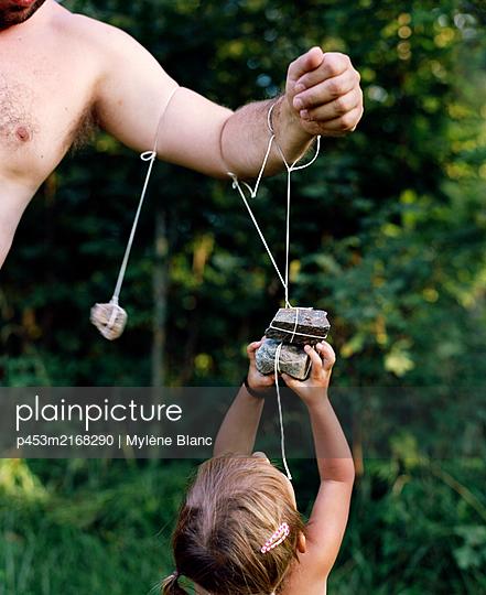 Mädchen spielt mit Steinen - p453m2168290 von Mylène Blanc