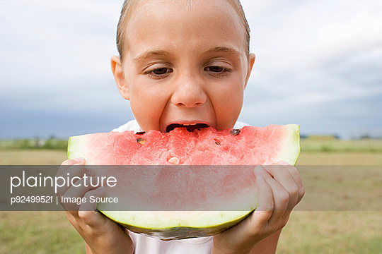 Girl eating a large slice of watermelon - p9249952f by Image Source