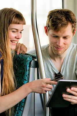 Junges paar in der Bahn schauen auf einem Tablet - p1212m1138819 von harry + lidy
