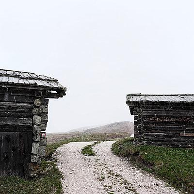 Feldweg zwischen zwei rustikalen Holzhütten - p1383m1589131 von Wolfgang Steiner