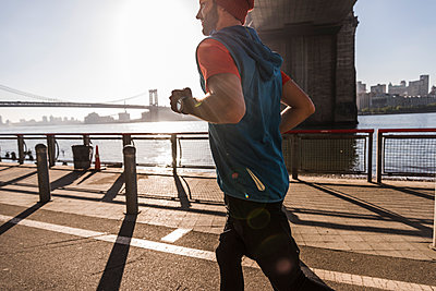 USA, New York City, man running at East River - p300m1192440 by Uwe Umstätter
