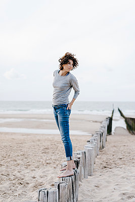 Woman standing on wooden stake on the beach - p300m1499375 by Kniel Synnatzschke
