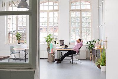 Man working at desk in a loft office - p300m2012523 by Florian Küttler
