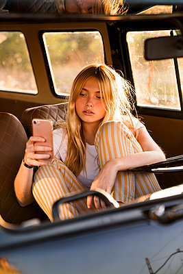 Young woman sitting in a van using cell phone - p300m2023499 by Kike Arnaiz