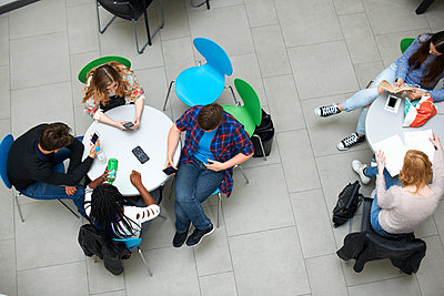 Group of friends sitting in cafeteria, elevated view - p429m1407896 by Peter Muller