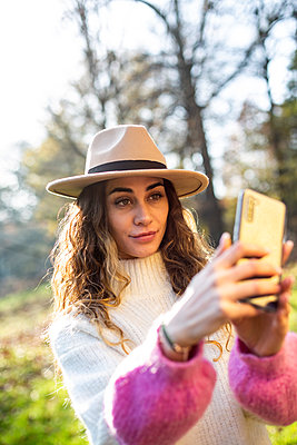 Young woman with hat takes a selfie in the park - p975m2222104 by Hayden Verry