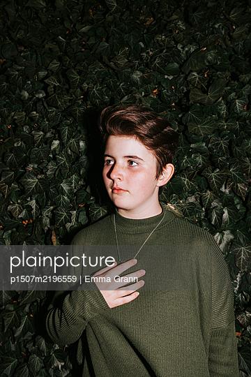 Teenage girl against green hedge - p1507m2196559 by Emma Grann