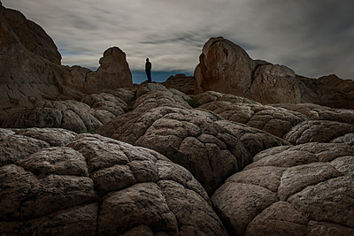 Low angle view of man standing on rock formations against cloudy sky - p1166m1186719 by Cavan Images