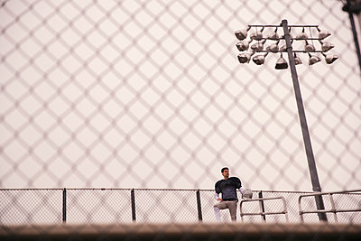 Low angle view of American football player looking away while standing in stadium seen through fence - p1166m1423133 by Cavan Images