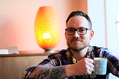 Mann mit Tattoo und Kaffeetasse - p1258m1196014 von Peter Hamel