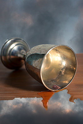 Worn silver chalice lying on a melting wooden shelf in the sky. - p1433m1589985 by Wolf Kettler