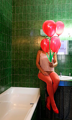 Woman holding balloons in a bathroom - p1521m2126575 by Charlotte Zobel