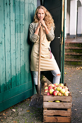 Portrait of confident woman standing at crate with apples - p300m1562211 by Peter Scholl