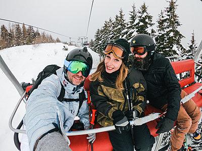 Italy, Modena, Cimone, portrait of happy friends in a ski lift - p300m2029457 von Juri Pozzi