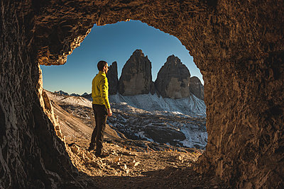 Italy, Tre Cime di Lavaredo, man hiking and standing in front of a cave with the three peaks in background - p300m2081528 by William Perugini