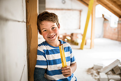 Smiling boy holding tape measure during house renovation - p300m2287715 by Epiximages